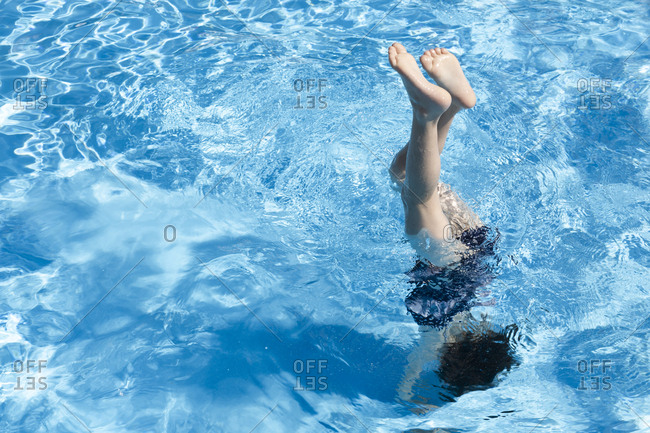 Little girl doing handstand in swimming pool