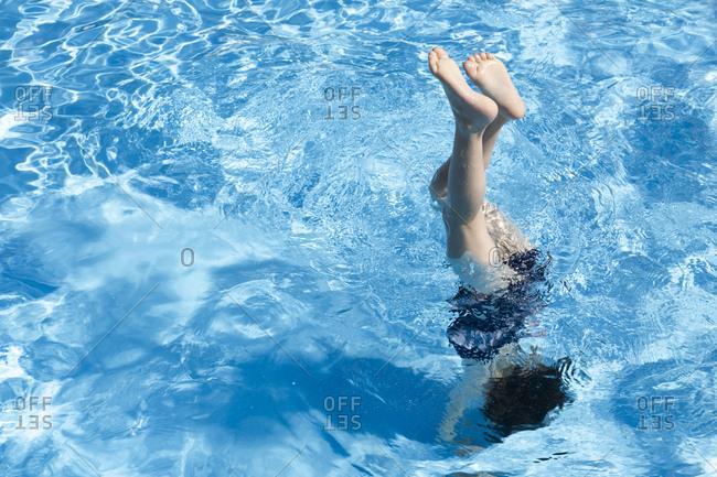 Little girl doing handstand in swimming pool