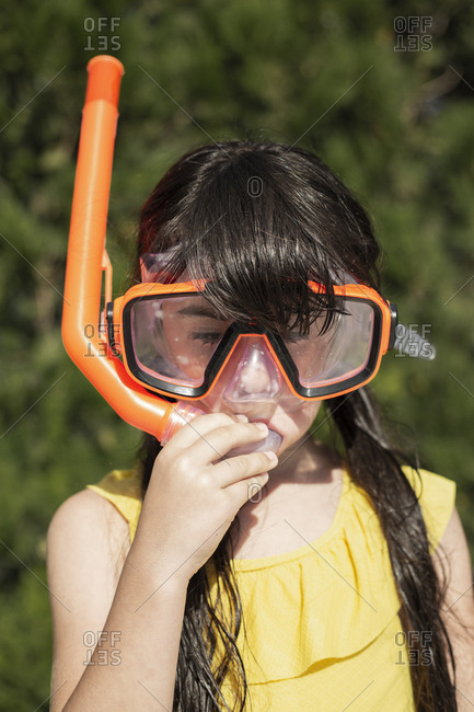 Portrait of little girl wearing snorkel and oversized diving goggles
