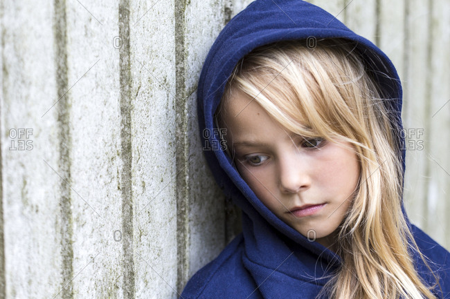 Portrait of sad blond girl wearing blue hooded jacket leaning against wooden wall