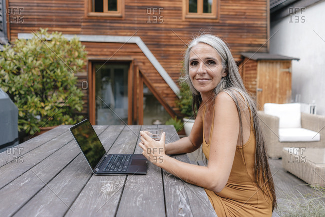 Portrait of smiling woman sitting on terrace of her house with laptop and glass of water