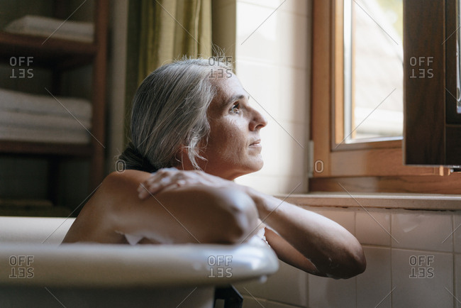 Portrait of pensive woman in bathtub looking out of window