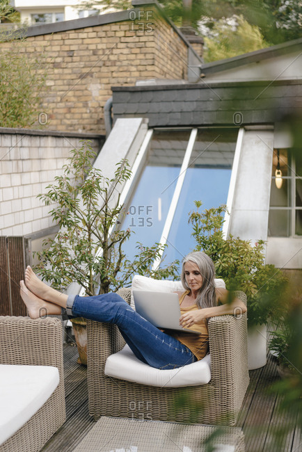 Woman relaxing on terrace using laptop