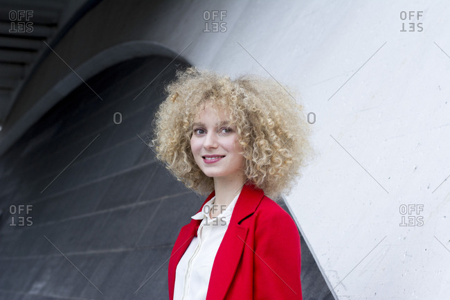 Portrait of smiling blond woman with ringlets wearing red suit coat