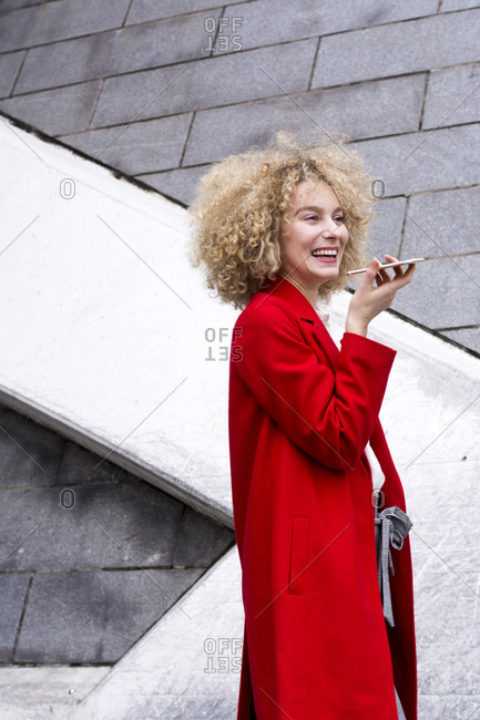 Portrait of laughing blond woman with ringlets wearing red coat talking on mobile phone
