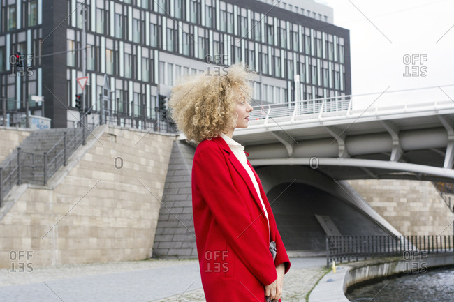 Germany- Berlin- blond young woman with ringlets wearing red coat