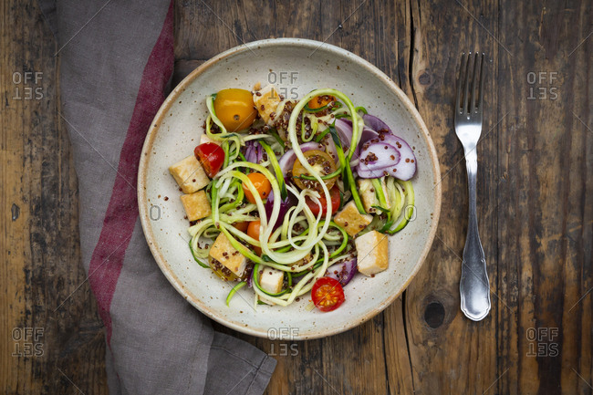 Bowl of zoodles with fried tofu- red quinoa- red onions and tomatoes