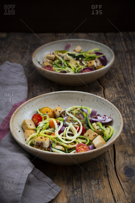 Two bowls of zoodles with fried tofu- red quinoa- red onions and tomatoes