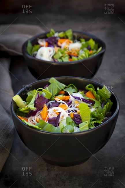 Two bowls of glass noodle salad with vegetables and peanuts