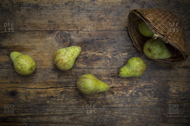 Organic pears 'Conference' and wickerbasket on dark wood