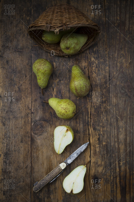 Whole and sliced organic pears 'Conference' with pocket knife on dark wood