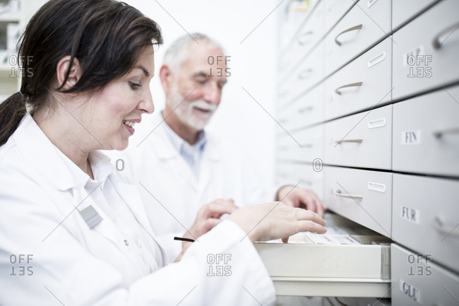 Two pharmacists at cabinet in pharmacy
