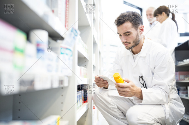 Pharmacist with pill box and prescription in pharmacy