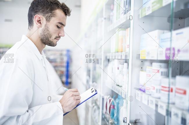 Pharmacist holding clipboard at shelf in pharmacy