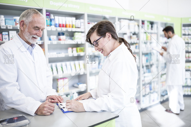 Two smiling pharmacists with clipboard at counter in pharmacy