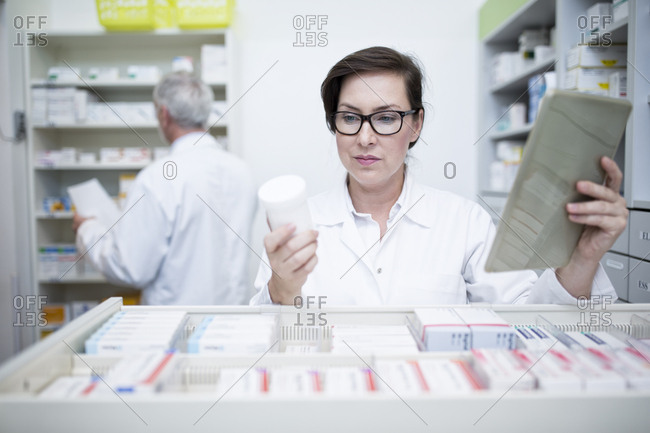 Pharmacist with tablet and medicine at cabinet in pharmacy