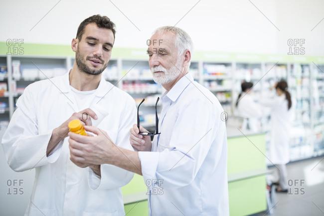 Two pharmacists examining medicine in pharmacy