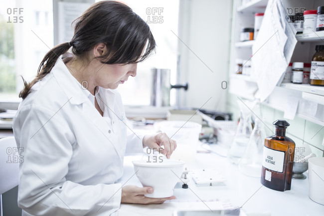 Woman preparing medicine in laboratory of a pharmacy