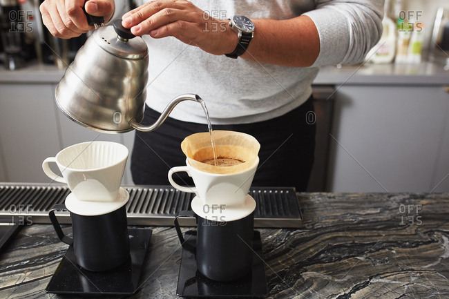 Man prepares two cups of pour over coffees with freshly ground beans