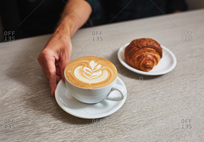A latte placed on a table next to a croissant