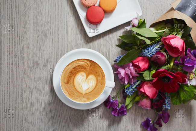Overhead view of a latte on a table next to a bouquet of flowers and macarons