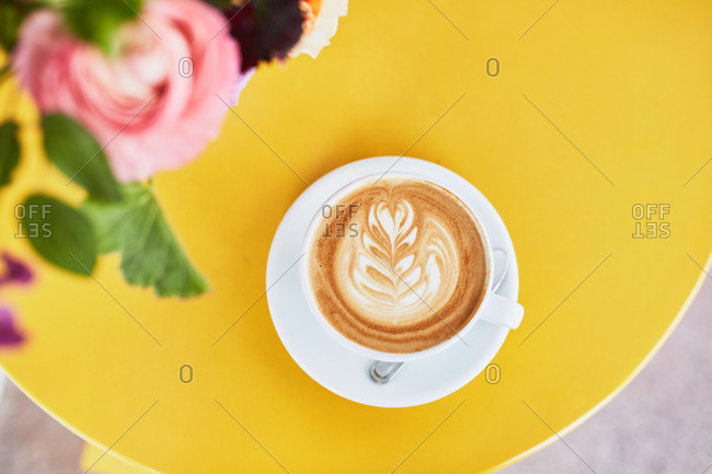 Close up overhead view of a latte on a table with flowers
