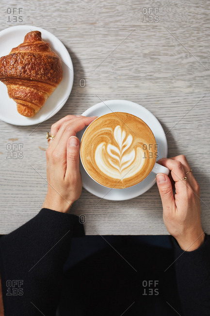Overhead view of a woman about to drink her latte