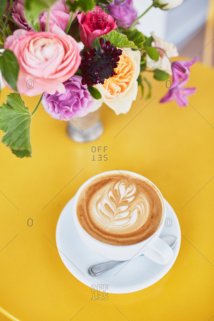 Overhead view of a latte on a table with flowers
