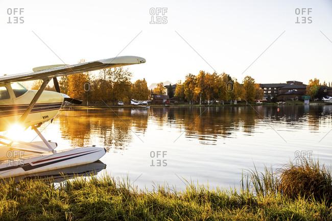 Seaplane docked on a lake at sunrise