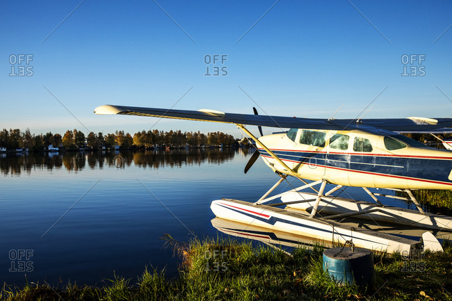 Blue skies over a seaplane docked on a lake