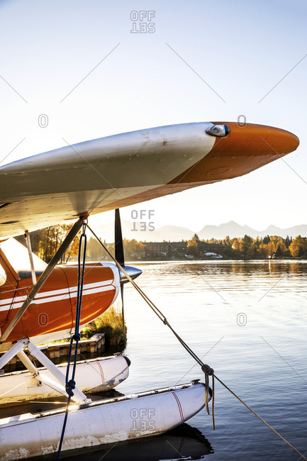 Side view of a seaplane docked at sunrise