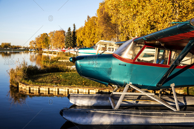 Seaplanes docked on a lake at sunrise