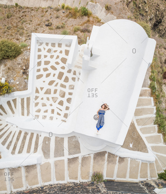 Aerial view woman lying on the roof on Santorini traditional house with surrounding staircase, Greece.
