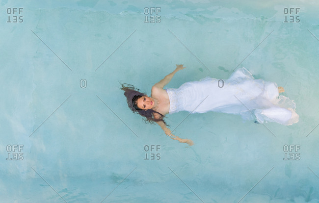 Aerial view above of an attractive woman floating in water in a wedding dress.