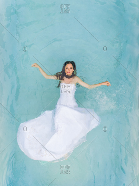 Aerial view of a beautiful woman in wedding dress floating in clear pool.