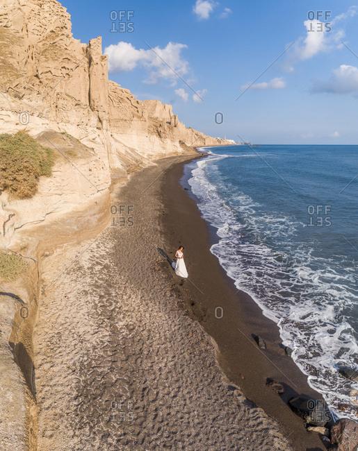 Aerial view of woman with wedding dress walking on beach on Santorini island, Greece.