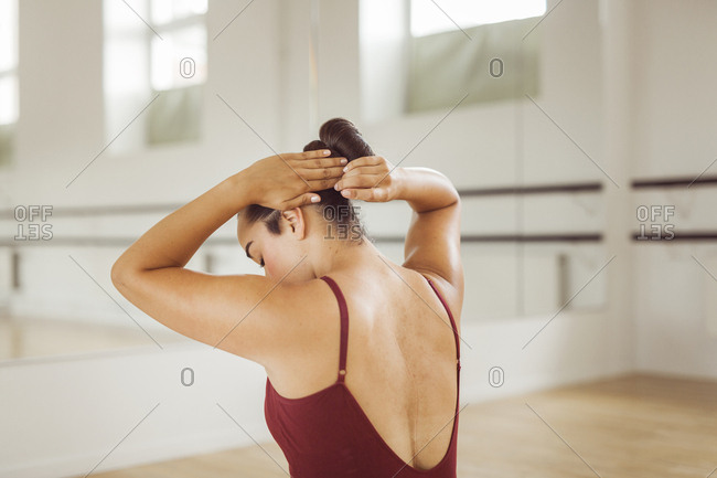 Rear view of ballerina adjusting hair