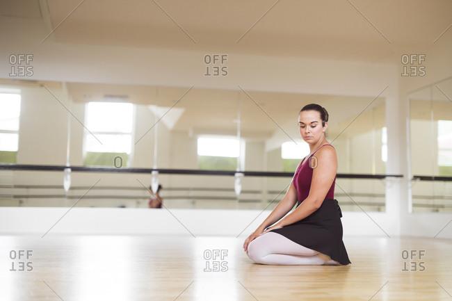 Ballerina sitting on wooden floor