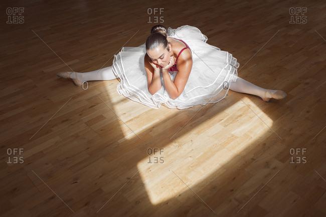 Ballerina stretching on wooden floor