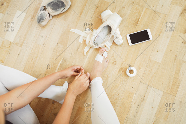 Low section of ballerina sitting on wooden floor