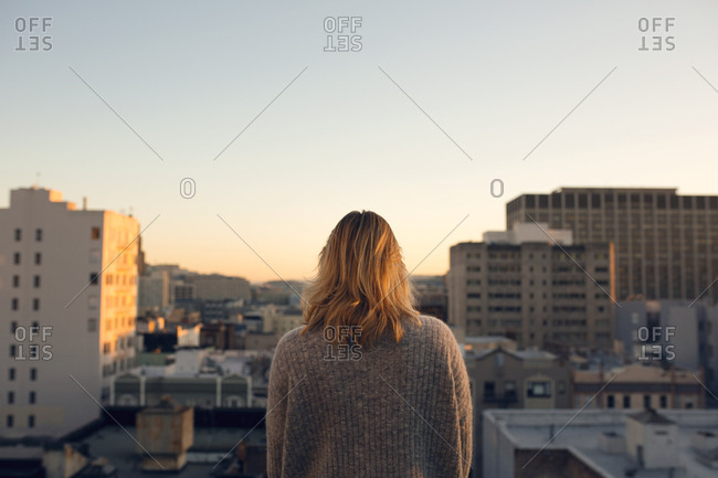 Rear view of blonde woman looking at city