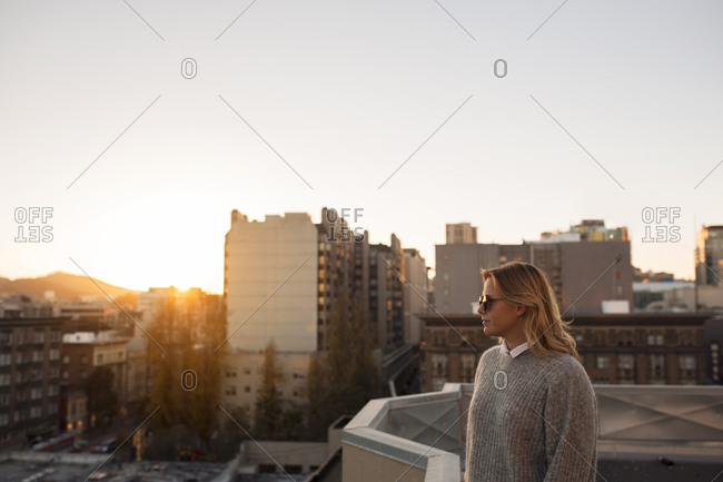 Woman standing on terrace at sunset