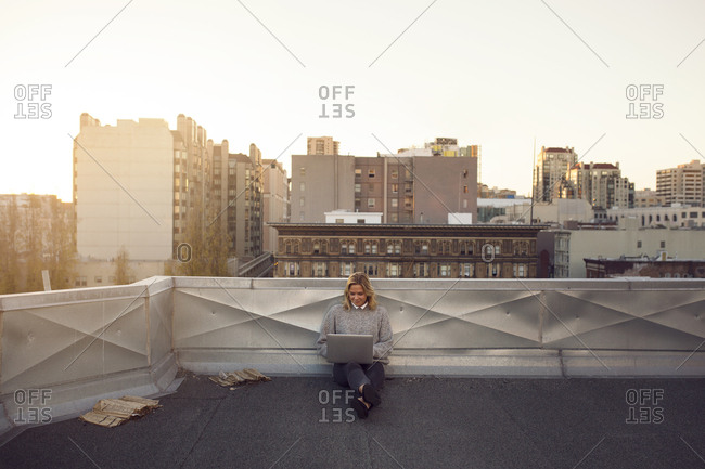 Woman sitting on terrace with laptop