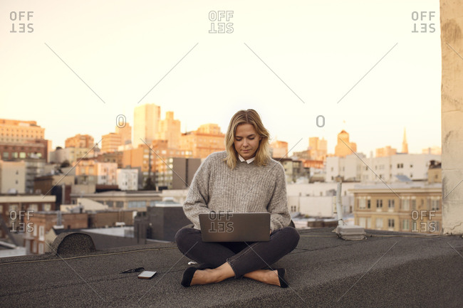 Woman sitting on roof and using laptop