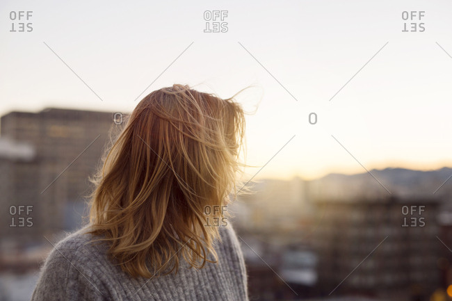 Young blonde woman in city at sunset