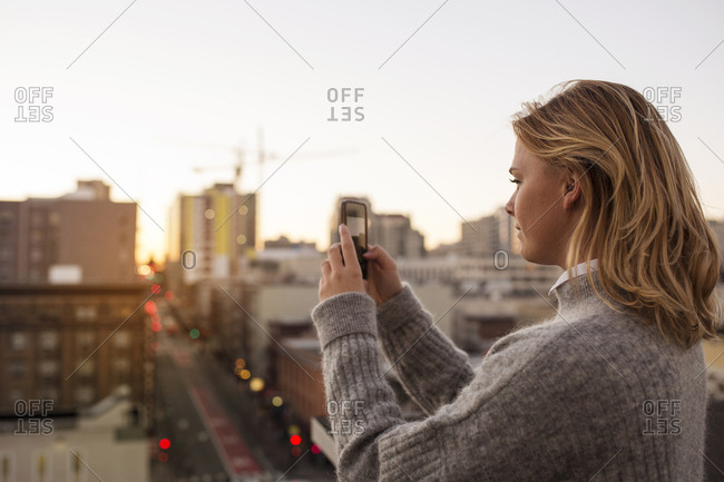 Young blonde woman photographing city at sunset