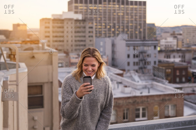 Young blonde woman using smart phone