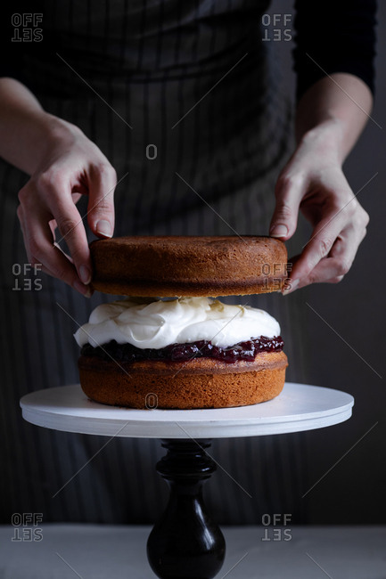 Female hands arranging victoria sponge cake with jam and whipped cream