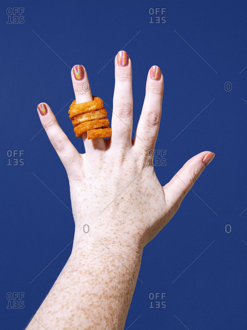 A hand with a curly french fry on the ring finger against a blue background.