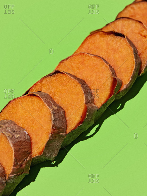 Slices of orange sweet potatoes lined up diagonally on a green background with a strong shadow.